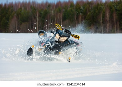 In snowdrift rider loss control and fall off from snowmobile. Reducing risk of injury by safety gear during backcountry tour accident. Extreme sport adventure, outdoor activity during winter holiday.