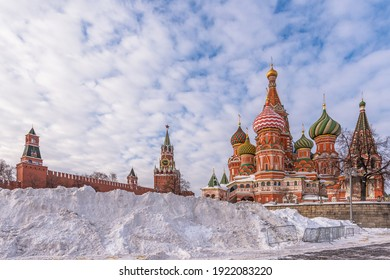 The snowdrifts on Vasilyevsky Spusk after heavy snowfall.  St. Basil's Cathedral, the famous Spasskaya Clock Tower and wall of the ancient Moscow Kremlin against a blue sky. Russia, Moscow.