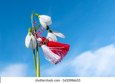 Snowdrops and martenitsa against the blue sky. Martisor flutters in the wind. March 1st - traditional trinkets. Baba Marta Day - Bulgarian holiday. Beginning of Spring Concept. Copy space.