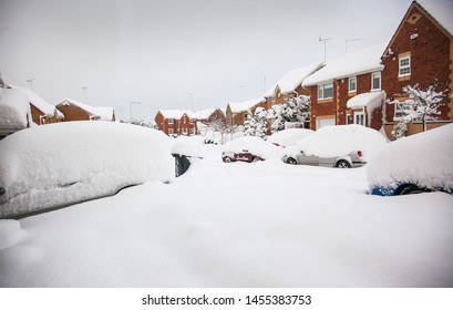 Snowed in - heavy snowfall on typical UK houses and cars