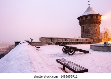 Snowed in historical cannon on the castle terrace at night with lighting