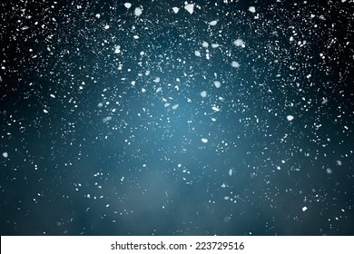 Snowfall with Blue Background - Fluffy snowflakes falling in front of a blue background with vignette
