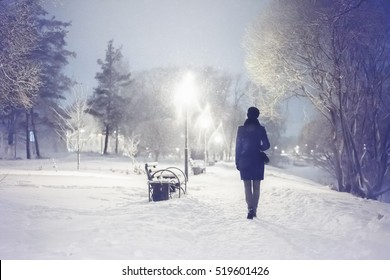 Snowfall in the city park. Woman walking down by alley. Night winter landscape with falling snowflakes. Winter snowfall scene. Severe weather in the winter park with trees, benches covered by snow.