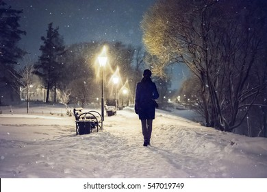 Snowfall in the city park. Woman walking down by alley. Night landscape with falling snowflakes. Severe weather in the winter park with trees, benches covered by snow.
