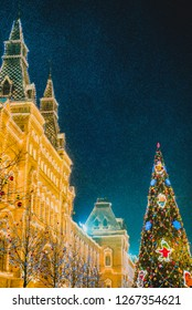 Snowfall, fine snow in backlight. Illuminated GUM facade and New year festive decorations on Red Square, main landmark in Moscow. Christmas fair in Russia at evening while snow falling