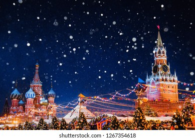 Snowfall, fine snow in backlight. Saint Basil cathedral and Spasskaya Tower among new year festive decorations on Red Square in Moscow. Christmas fair in Kremlin of Russia at evening