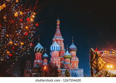 Snowfall, fine snow in backlight. Saint Basil cathedral among new year festive decorations on Red Square in Moscow. Christmas fair in Russia at evening while snow falling