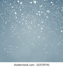 Snowfall with Light Blue Background - Fluffy snowflakes slowly falling in front of a light blue background with vignette