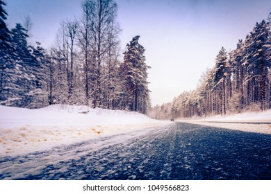 Snowfall on a winter day, car rides along road passing through the forest into the snow. Close up view from the asphalt level. Coniferous forest. Russia, Europe. Beautiful nature. Orange-purple toning
