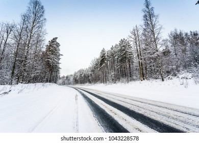 Snowfall on a winter day, snow-covered country road. View from the side of the road. Coniferous forest. Russia, Europe. Beautiful nature.