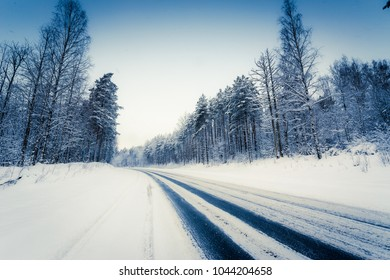 Snowfall on a winter day, snow-covered country road. View from the side of the road. Coniferous forest. Russia, Europe. Beautiful nature. Yellow-blue toning effect.