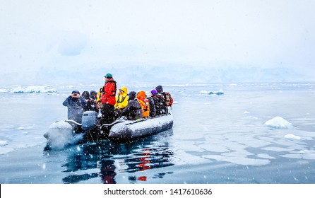 Snowfall over the boat with frozen tourists drifting among icebergs, near Almirante Brown, Antarctic peninsula