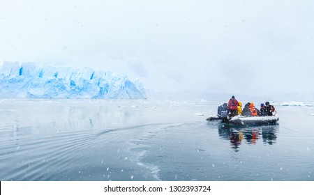 Snowfall over the motor boat with frozen tourists drifting across cold sea with glacier in the backgroynd, near Almirante Brown, Antarctic peninsula