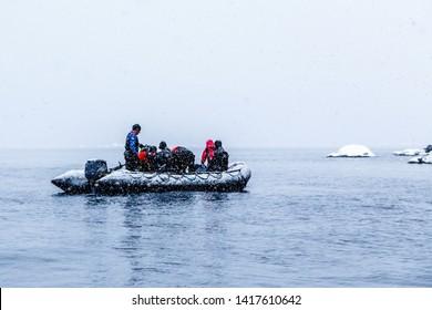 Snowfall over the Zodiac boat with frozen polar divers near Almirante Brown, Antarctic peninsula