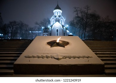 snowfall in Vladivostok. An evening look in the downtown. Memorial - an eternal flame in the square of Vladivostok