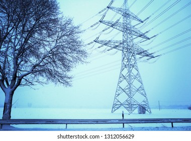 Snowfall in winter,  landscape with tree and high voltage pylon