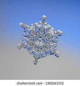 Snowflake glittering on blue gradient background. Macro photo of real snow crystal: elegant star plate with six short arms, fine hexagonal symmetry, glossy relief surface and complex inner details.