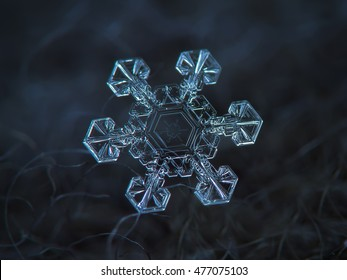 Snowflake glowing on dark blue wool background. This is macro photo of real snow crystal: large stellar dendrite with short and broad arms, and interesting pattern inside central hexagon.