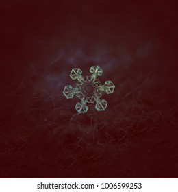 Snowflake glowing on dark textured background. Macro photo of real snow crystal: star plate snowflake with short, simple arms and big, transparent center with unusual pattern inside.