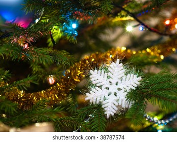 Snowflake and golden tinsel on a Christmas tree