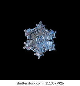 Snowflake isolated on black background. Macro photo of real snow crystal: elegant star plate with glossy relief surface, fine hexagonal symmetry, short, broad arms and complex inner patterns.