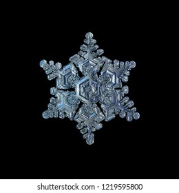 Snowflake isolated on black background. Macro photo of real snow crystal: complex star plate with fine hexagonal symmetry, six short, broad arms and glossy relief surface with intricate inner details.
