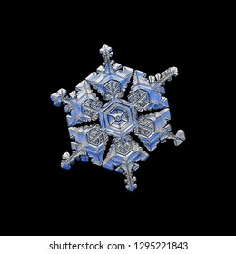 Snowflake isolated on black background. Macro photo of real snow crystal: complex, big star plate with fine hexagonal symmetry, glossy relief surface, six short, ornate arms and elegant inner pattern.