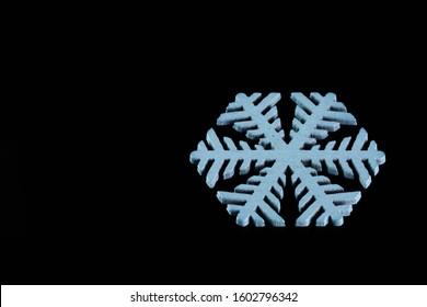 Snowflake isolated on black background: macro photo.