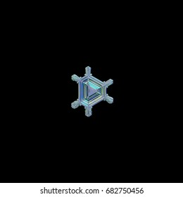 Snowflake isolated on black background. Macro photo of real snow crystal of rare triangular type with six short, simple arms and glossy, relief center with pattern of straight lines and ridges.