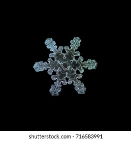 Snowflake isolated on black background. Macro photo of real snow crystal at high magnification: stellar dendrite snowflake with beautiful inner pattern, simple arms and asymmetrical central hexagon.