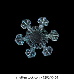 Snowflake isolated on black background. Macro photo of real snow crystal with simple shape, fine hexagonal symmetry, six short, broad arms and unusual pattern in center.