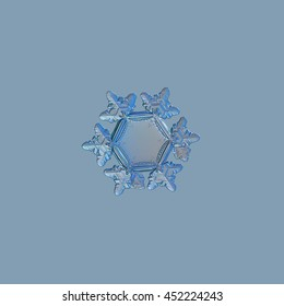 Snowflake isolated on pale blue background. This is macro photo of real snow crystal with unusually big, flat and empty central hexagon, and highly detailed outer rim and short arms with ridges.
