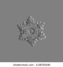 Snowflake isolated on uniform gray background. Macro photo of real snow crystal: stellar dendrite with fine hexagonal symmetry, glossy relief surface, large central hexagon and six short, ornate arms.