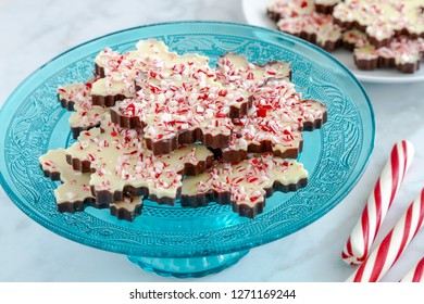 Snowflake shaped chocolate peppermint bark on blue glass platter with additional plate in background and red and white striped peppermint sticks on the side