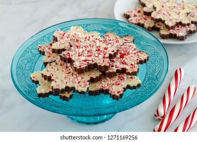 Snowflake shaped chocolate peppermint bark on blue glass platter with additional plate in background and red and white striped peppermint sticks