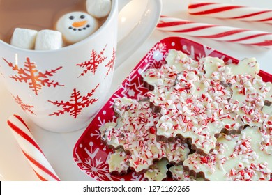 Snowflake shaped chocolate peppermint bark on holiday platter with mug of hot cocoa with marshmallows and snowman decoration