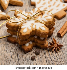 Snowflake shaped Gingerbread cookies stacked and tied with a gold bow.