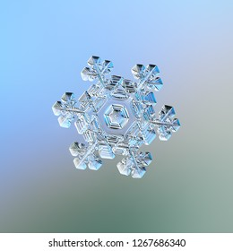 Snowflake sparkling on smooth gradient background. Macro photo of real snow crystal: elegant star plate with fine hexagonal symmetry, short ornate arms, glossy relief surface, complex inner pattern.