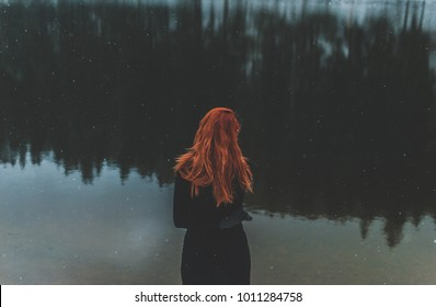 Snowflakes flying over handsome black-eyed redhead girl looking in the distance. White snowflakes flying all around. Splendid shady black mountain lake. Look from behind