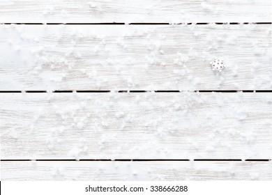Snowflakes on wooden blank table, white flakes of snow on light xmas desk, merry Christmas holiday background card pattern, happy new year  copy space. Top view from above. Empty background, backdrop.
