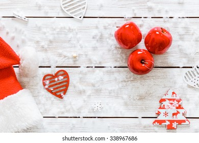 Snowflakes, Santa claus hat, hearts and red apples on wooden empty blank table with white snow, xmas background, copy space, top view from above, merry Christmas holiday card pattern, happy new year