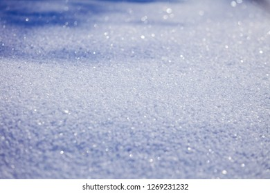 Snowflakes in the snow close up. Blurred blue background.