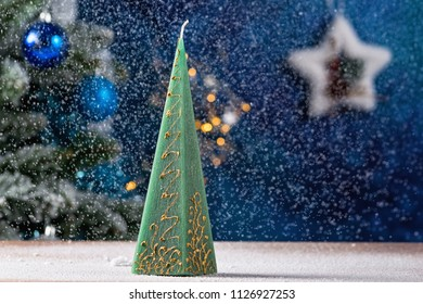 Snowing background with green pyramid candle and christmas tree in the background