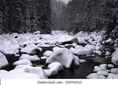 Snowing on a river with stones covered by snow