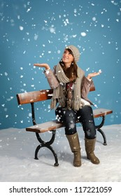 snowing on a woman seated on a bench, blue background