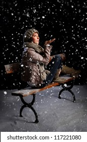 snowing on a woman seated on a bench at night