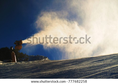Snowmaking on slope. Skier near a snow cannon making fresch powder snow. Mountain ski resort and winter calm mountain landscape.