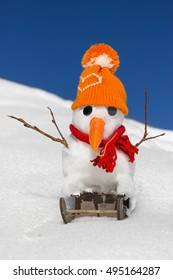 A snowman with arms out of branches is sitting on a sled