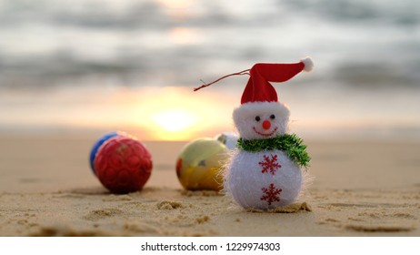 Snowman with ball Christmas decorations on beach with sunset and blurred sea blackground