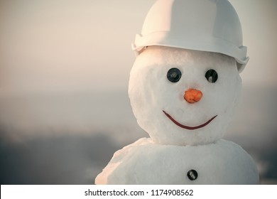 Snowman builder in helmet. Happy holiday and celebration. Christmas or xmas decoration. New year snowman from snow in winter. Building and repair work.